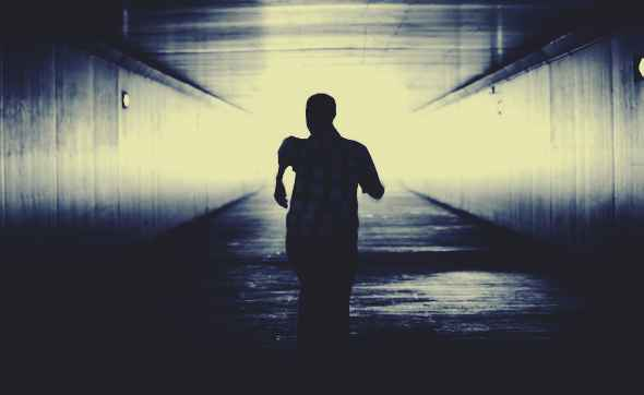 man running down a dark alley